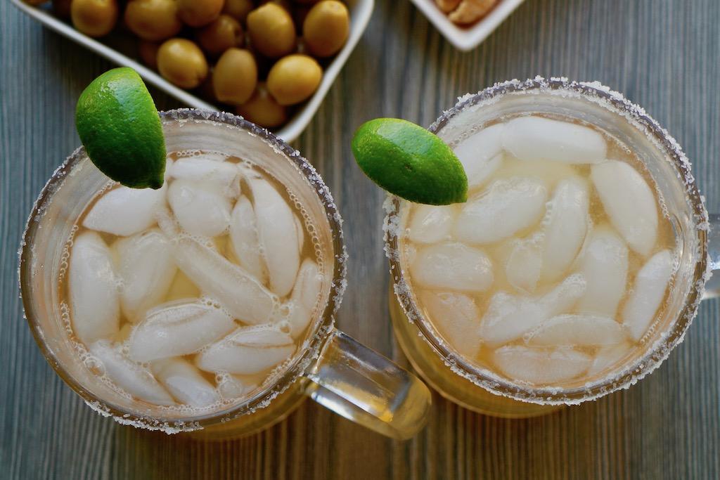 dos jarras de cerveza micheladas con limón y botanas