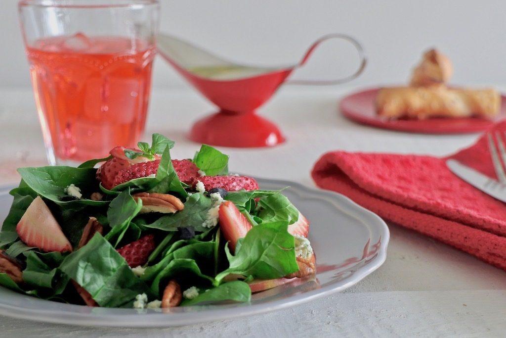 ensalada servida sbre plato gris con props en rojo