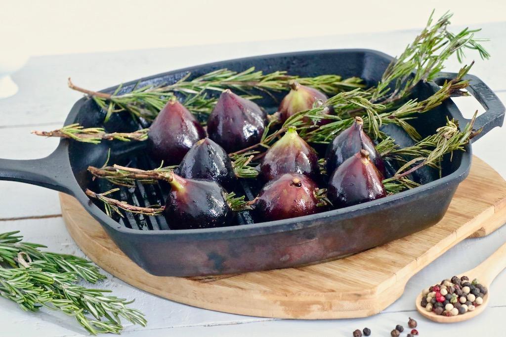 Higos ensartados en ramas de romero y colocados dentro de grill