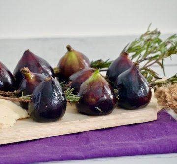 Higos, romero y queso sobre tabla y servilleta morada