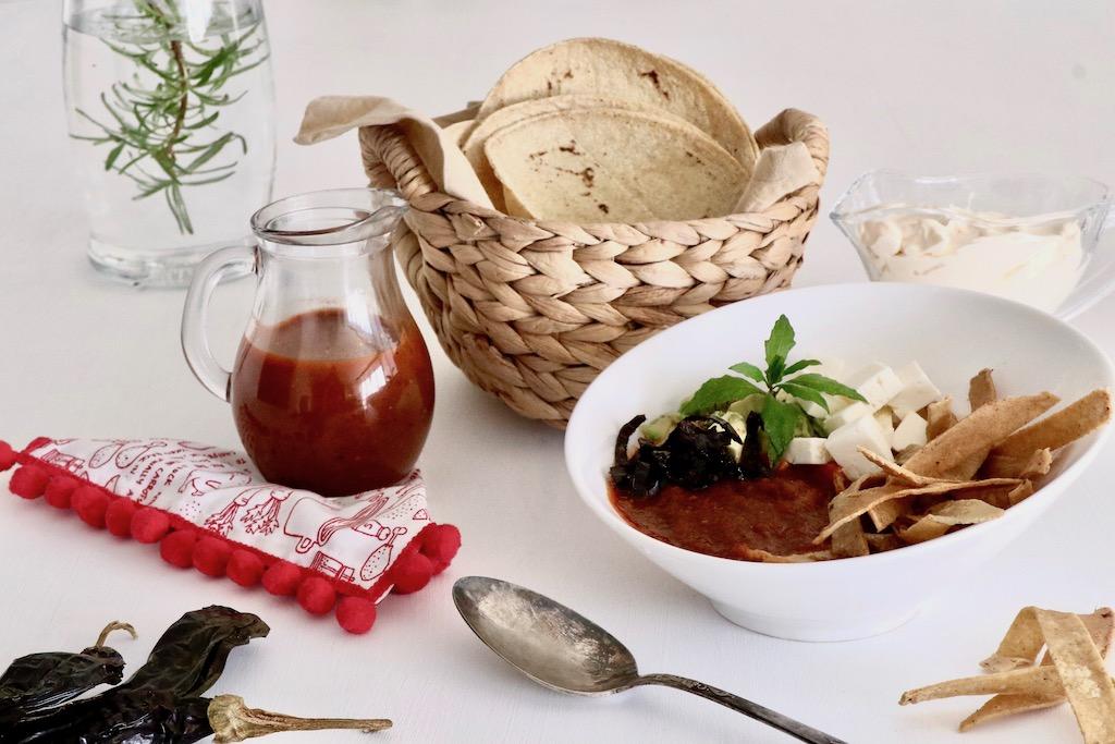 sopa de tortilla y huachinango con pico de gallo. Sopa de tortilla en bol blanco y canasta con tortillas