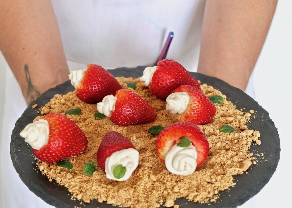 Plato de strawberry cheesecake sin azúcar en las manos